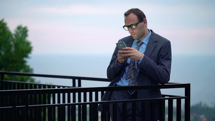 Young businessman using, texting on smartphone on terrace