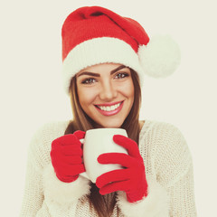 Santa girl with white mug. Christmas woman with tea cup.