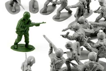 toy army men surrounding a single opponent