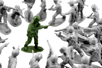 toy green army man surrounded by enemy soldiers
