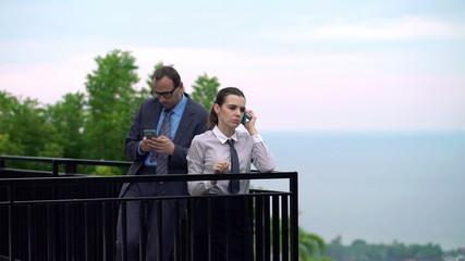 Businesswoman talking on cellphone, man using smartphone on terr