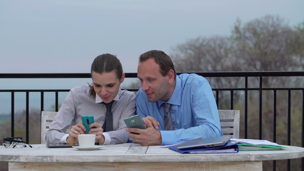 Business couple watching funny things on smartphones on terrace