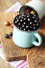 Ripe blackcurrants and gooseberries in mug