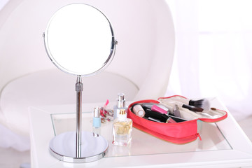 Cosmetic bag and mirror on table on light background