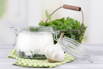Glass round bowl of cream with a tuft of dill and pepper near