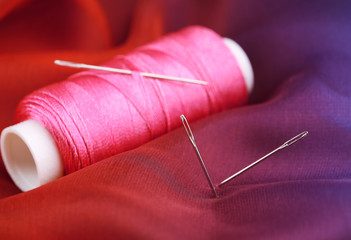 Needles and spool of thread on color fabric background