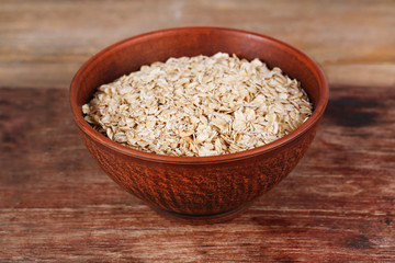 Big bowl with oatmeal on a wooden stand on a table