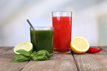 Glasses of vegetable juice with lime and lemon on wooden table