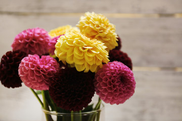 Dahlia flowers in vase on wooden table