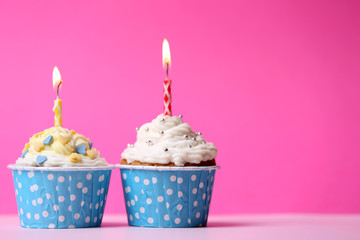 Delicious birthday cupcakes on table on pink background