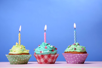 Delicious birthday cupcakes on table on blue background