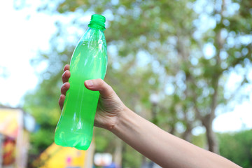 Hand holds bottle with sweet water on bright background