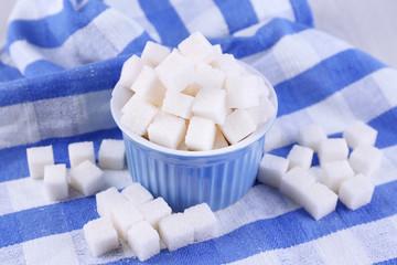 Refined sugar in color bowl on color napkin background