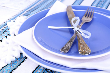 Blue plates, knife, fork, napkin and Christmas decoration