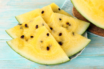 Slices of yellow watermelon on wooden background closeup