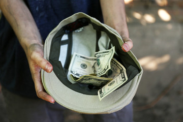Homeless beggar money on his hat