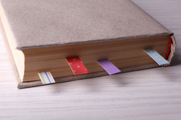 Book with bookmarks on wooden background