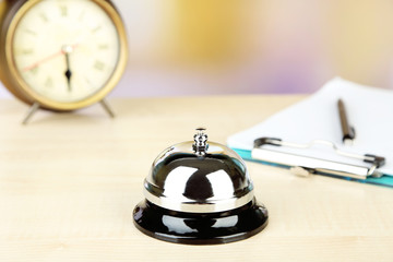 Reception bell on hotel reception desk, on bright background
