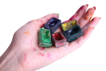 Watercolor paint cubes in female hand isolated on white
