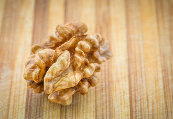Kernel walnut on wood background. Selective focus.