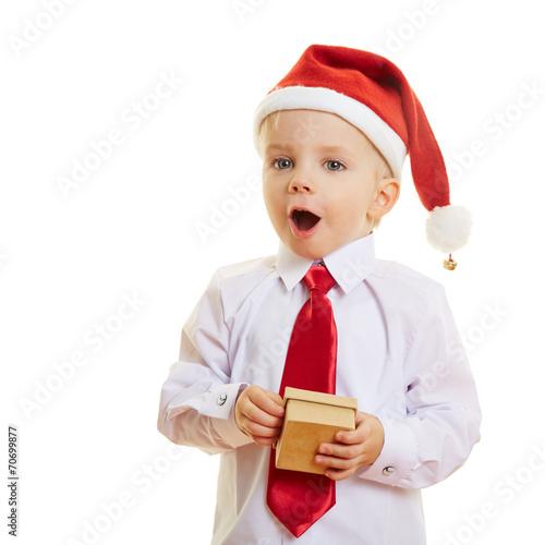 canvas print picture Kind zu Weihnachten freut sich über Geschenk