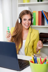 Beautiful young woman listening to music in the office