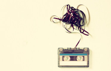 Cassette tape over wooden table with tangled ribbon. top view. r