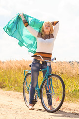 Happy blonde girl at cycling on dirt road