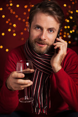 Christmas - man with a glass of wine talking on mobile phone