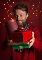 Christmas - smiling man holds pile of presents on dark red