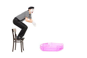 Mime artist jumping into a small inflatable pool i