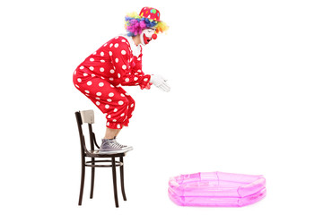 Male clown preparing to jump into a small pool