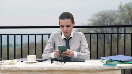 Businesswoman texting on smartphone by the table on terrace