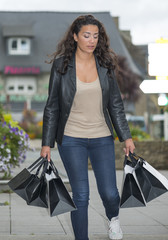 Young woman with full of bags walking in the street