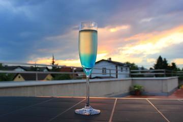 Cocktail mit Sekt und Blue Curacao vor Abendhimmel