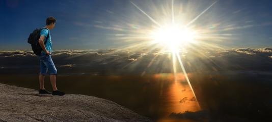 Tourist on mountain. Storm darkness & sun-shining sky