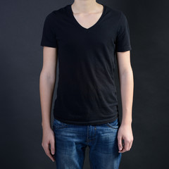 Young man in blank black t-shirt over dark background, teen boy