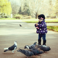 Cute fashionable baby girl feeding a pigeons at the autumn park