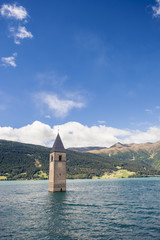 sunken church tower in lake in the alps