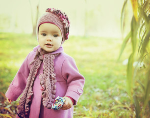 Cute liitle girl playing in autumn park, nature outdoor