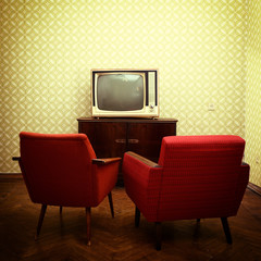 Vintage room with two old fashioned armchairs and retro tvover o
