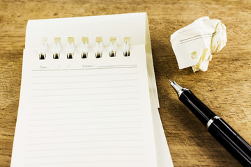 Blank notepad and crumpled with pen on wooden desk