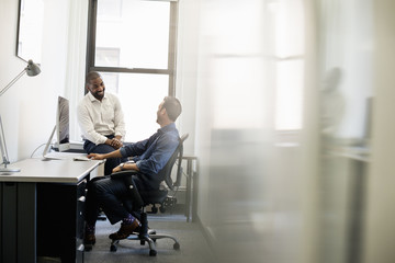 Office life. A man leaning back in an office chair talking to a colleague sitting on the edge of the desk.