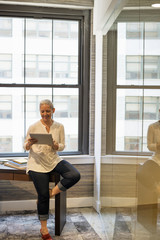 Office life. A woman seated on the edge of her desk using a digital tablet.