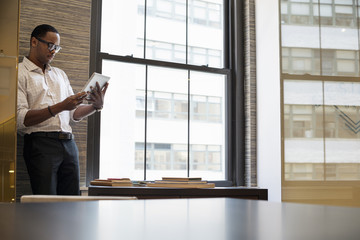 A man standing by a window in an office using a digital tablet.