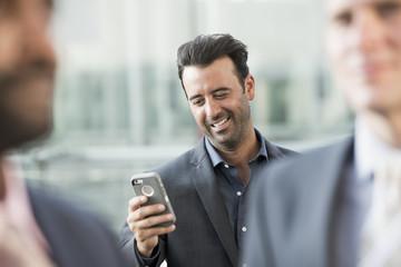 Three businessmen, one checking his smart phone.