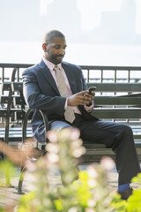 A businessman seated checking his phone, smiling.