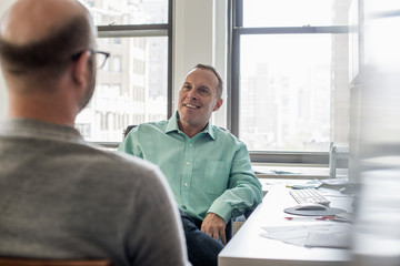 Two men seated in a light airy office environment, talking.