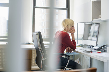 Office life. A woman sitting at a desk using a computer, looking intently at the screen.