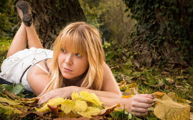 beautiful girl lying down in a forest with autumn leaves